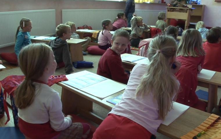 In roten Farben gekleidete Kinder in einer bayerischen Waldorfschule.